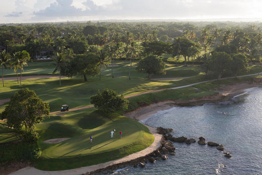 aerial view people playing golf on a golf course next to the ocean at Casa de Campo