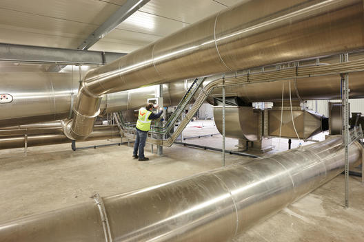 man in top floor of waste treatment technology plant (recycling technology; producing gas and compost from biological waste)