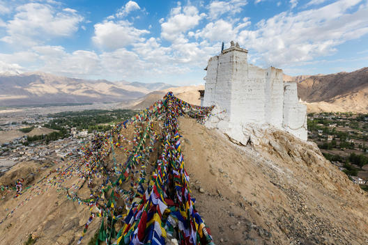 Low angle view of colorful prayer flags under hillside monastery, Leh, Ladakh, India