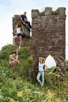 Group of young people climb wall in the fields
