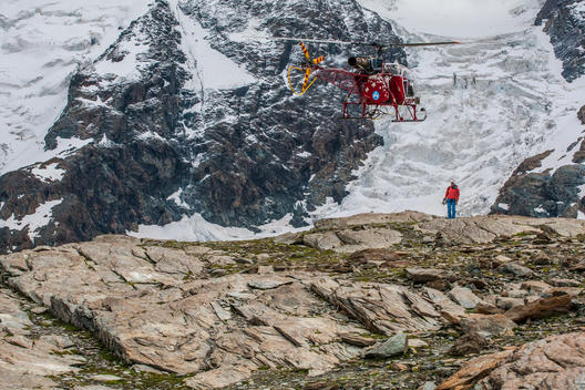 Air Zermatt rescue helicopter picking up a mountain guide to help the hotel rescue crew