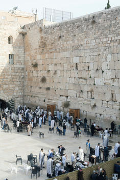 Celebrating at the Kotel, also known as the Western Wall, an ancient limestone wall in the Old City of Jerusalem. The wall is one of the holiest sites in Judaism. Men and women are separated from praying together by a barrier.