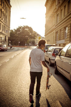 Man walking down European city with skateboard in hand during sunset.