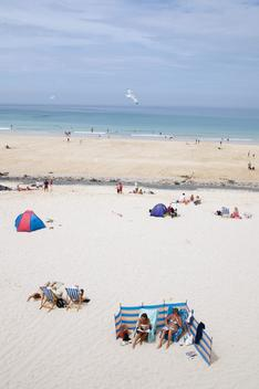 Holidaymakers sunbathe and relax on Porthmeor Beach. Surfers paddle out on the sea.