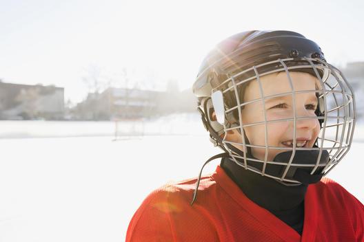 Smiling boy in ice hockey helmet looking away