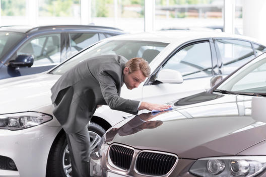 At the car dealer, Salesman cleaning car hood