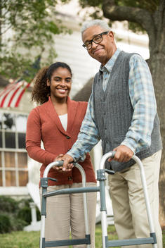 African American woman helping father use walker