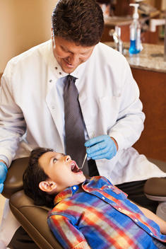 Dentist examining patient\'s teeth