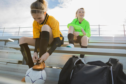 Soccer player sitting on bleachers tying shoelaces