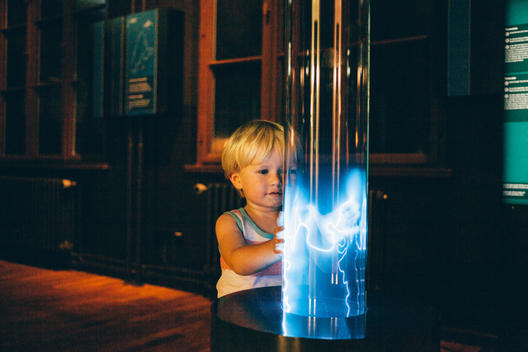 2 year old blonde boy playing with blue electric current at the Berlin Museum of Technology.