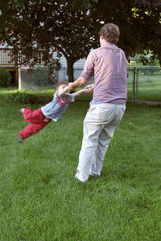 Man swinging child in yard.