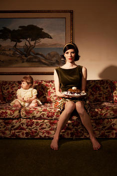 Elegant Woman Wearing Retro Clothing Holding A Dessert While Sitting On A Sofa With Her Baby
