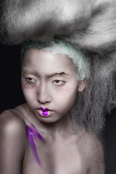Studio beauty tight cropped portrait of an Asian female model with artistic, purple makeup smeared on a shoulder and one lip, face is deconstructed long white hair is tied up, on a black background.
