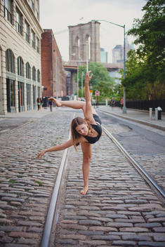 A young female dancer holding a dance pose in Dumbo with the Brooklyn Bridge in the background.