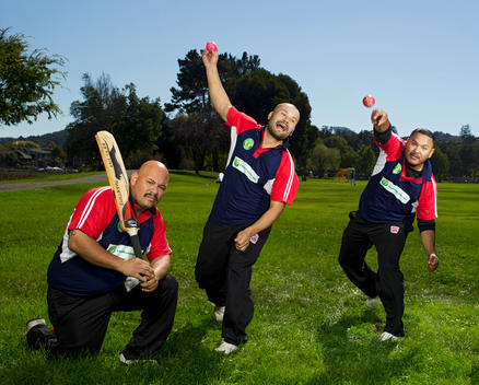One member of a cricket team kneels holding a bat while two other members throw balls on a field