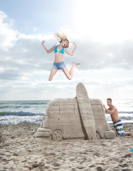 Young man working on sand castle van on the beach as woman is jumping in the air