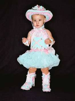 Child Beauty Pageant Contestant Wearing Frilly Cowboy Hat And Boots