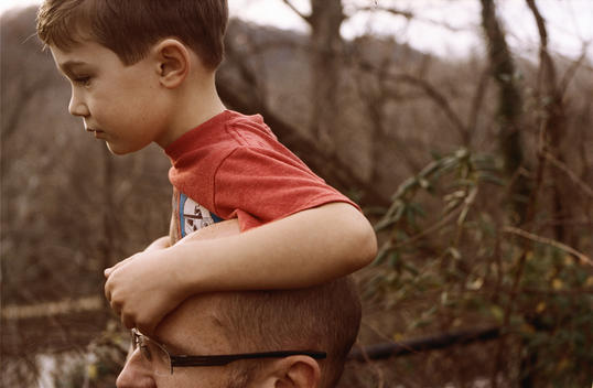 A young boy sitting on the shoulder of his father