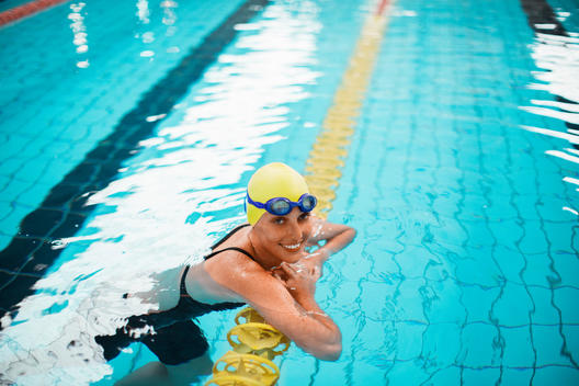 Portrait of smiling swimmer leaning on swimming lane marker in pool