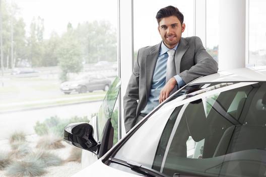 At the car dealer, Man standing at new car