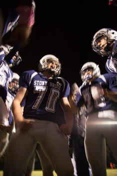 Low angle view of high school football players in a huddle