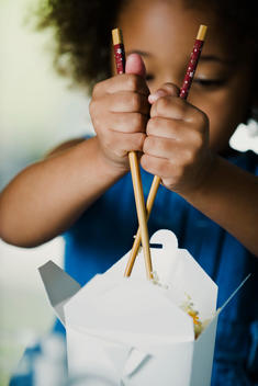 Little girl struggling to eat takeout food with chopsticks