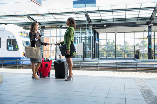 Businesswomen talking on train platform