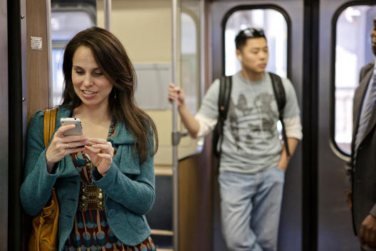 A Woman Uses Her Phone While On A Chicago L Train.