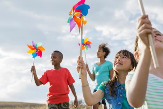 Smiling children holding pinwheels during field trip