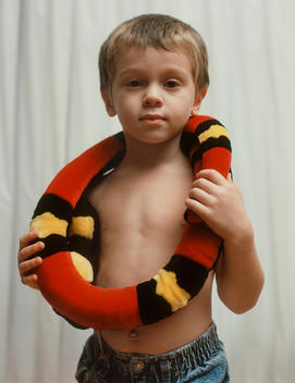 A Portrait Of A Boy With A Stuffed Animal Snake Wrapped Around His Neck.