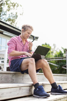 Man using hands-free device and laptop while sitting on porch against clear sky
