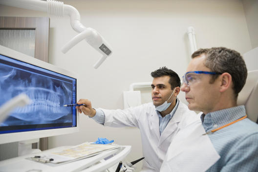 Dentist explaining tooth x-rays to patient
