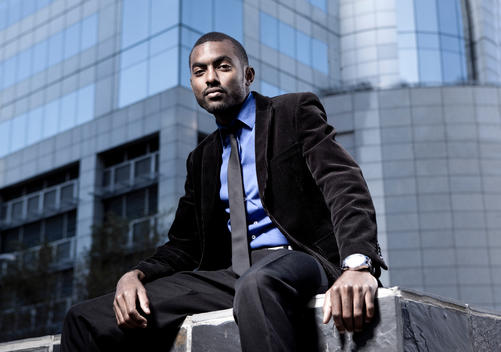 Southafrica, young African business man wearing black suit sitting in front of an office building