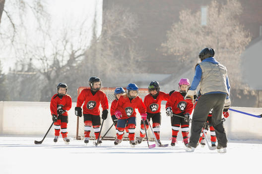 Coach guiding ice hockey team on rink