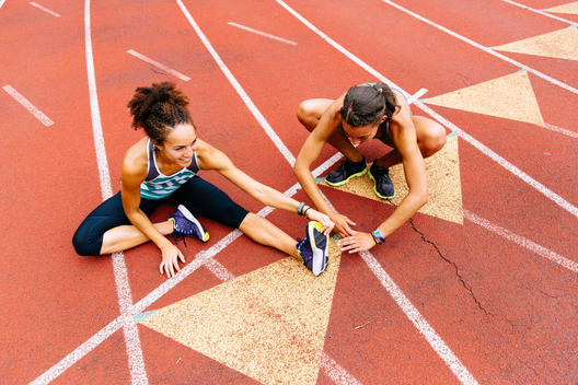 Two women stretching before a workout on a running track.