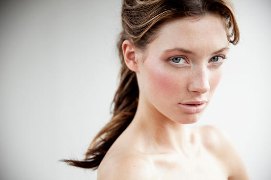 Close up beauty shot of a girl with hair tied up in front of a white wall in natural light.