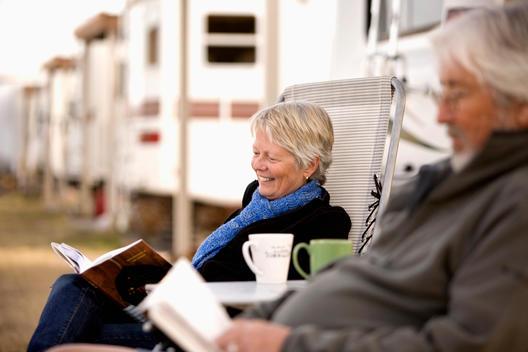 Senior Caucasian couple reading outside motor home