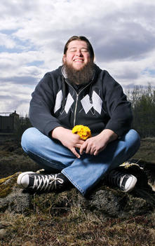 Happy Bearded Man Sitting In Field With Flowers