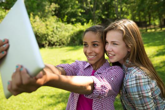 Two Girls Sitting Outdoors On A Bench, Using A Digital Tablet. Holding It Out At Arm\'S Length.