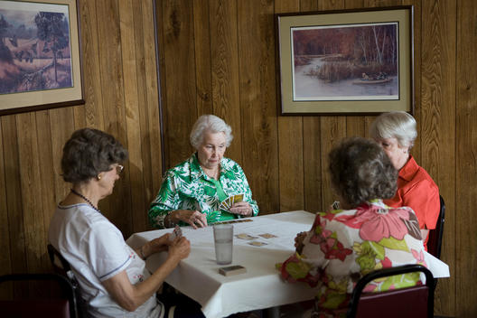 Group Of Senior Women Play A Game Of Bridge In Back Room Of Local Diner
