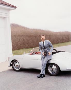 Man In Vintage Formal Attire Holding Camera Leans Against Vintage Car