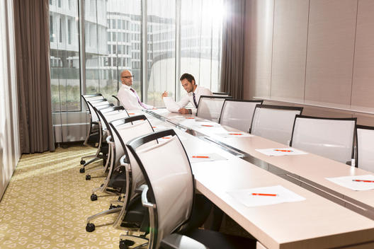 Poland, Warzawa, two businessmen sitting at conference room in hotel