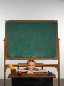 A well-groomed, young girl rests her head on her hands at a school desk in front of a chalkboard