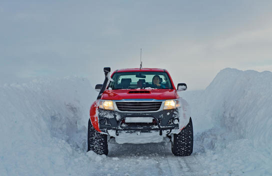Mature woman driving red pick up truck on snow covered road, Vikurskard, North Iceland