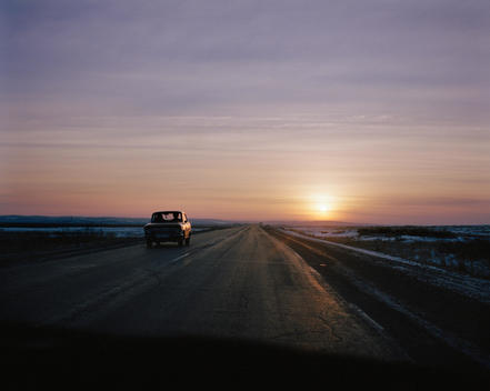 A Russian Travant Car Driving On A Road At Sunset, Seen Through The Windscreen Of A Car Traveling In The Opposite Direction.