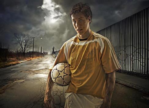 Illustration of soccer player holding ball on city street