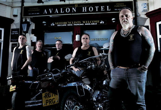 Portrait Of Group Of Bikers In Motorcycle Club Looking Tough