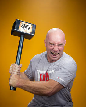 Arm wrestling competitor Todd Hutching screams as he holds a sledge hammer up