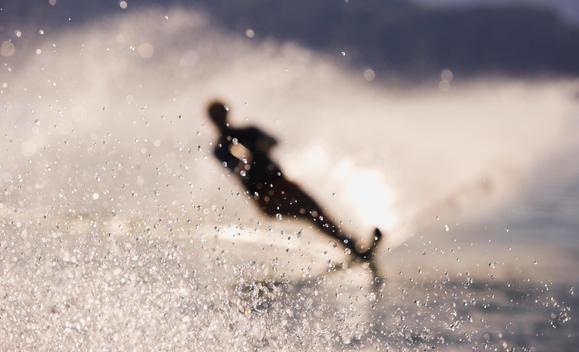 Austria, Salzkammergut, Lake Mondsee, Water-skier, silhouette (blurred motion)