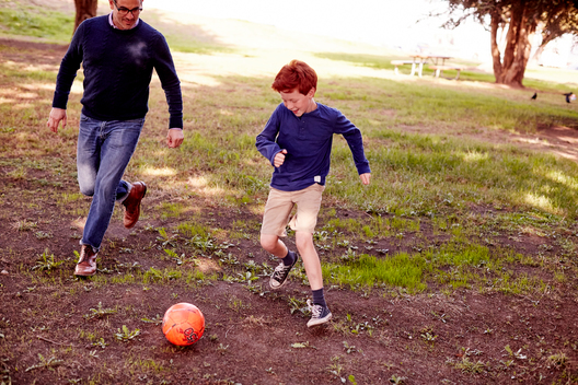 Redhead boy kicking soccer ball with father in park